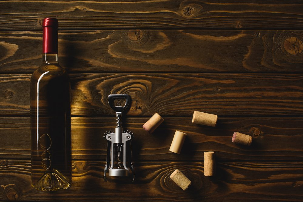 A bottle of white wine and some corks scattered on a wooden table top. Alcohol is not good for the symptoms of seasonal affective disorder