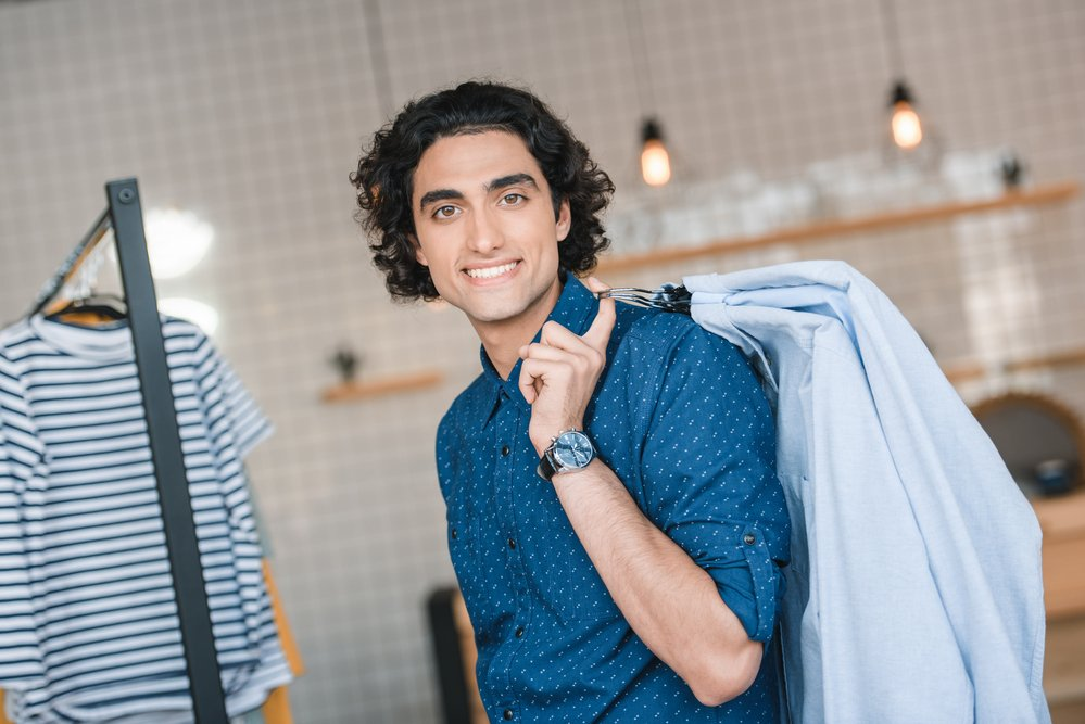 A smiling young man holding hangers full of shirts in a boutique. It's important to protect your smile when playing sport