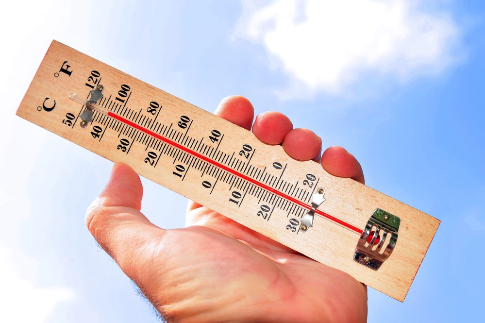 Thermometer being held on a hot sunny day