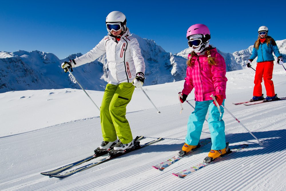 Child learning to ski with instructor