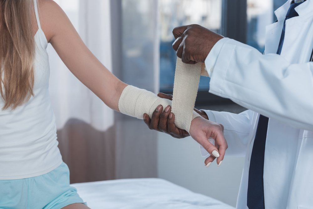 Doctor wrapping a bandage around an injured woman's arm