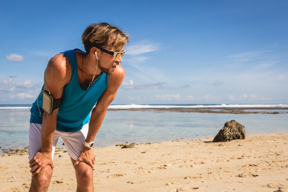 A tired sportsman, bent over, resting on a beach. He is suffering from burn out from excessive exercise
