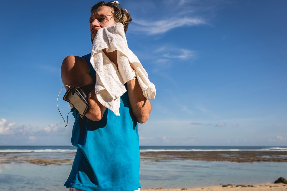 A man in a blue running top, wiping down on a beach in the sunshine