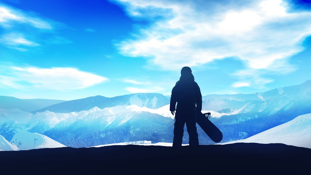 Dark silhouette of a snowboarder standing on a hillside opposite a bright blue sky.  Avoiding winter injuries takes care and preparation.