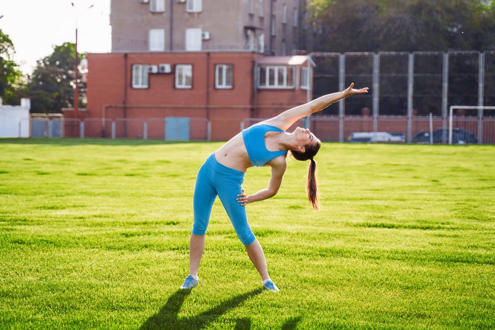 25 year old woman stretching in a park