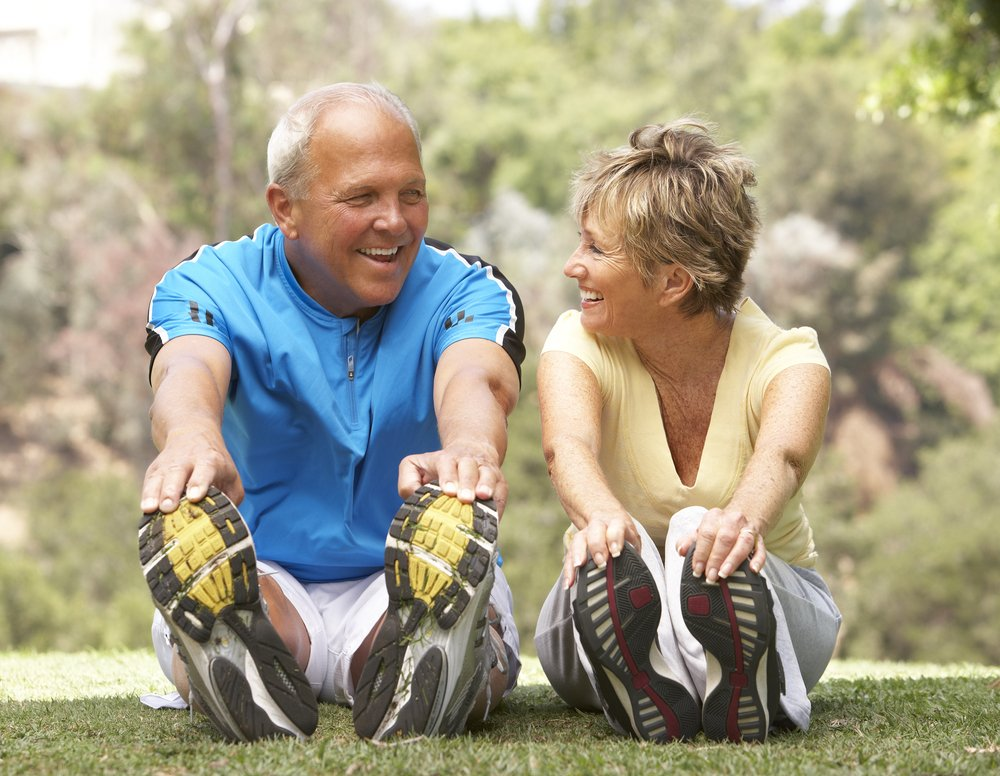 Older couple exercising happily outdoors