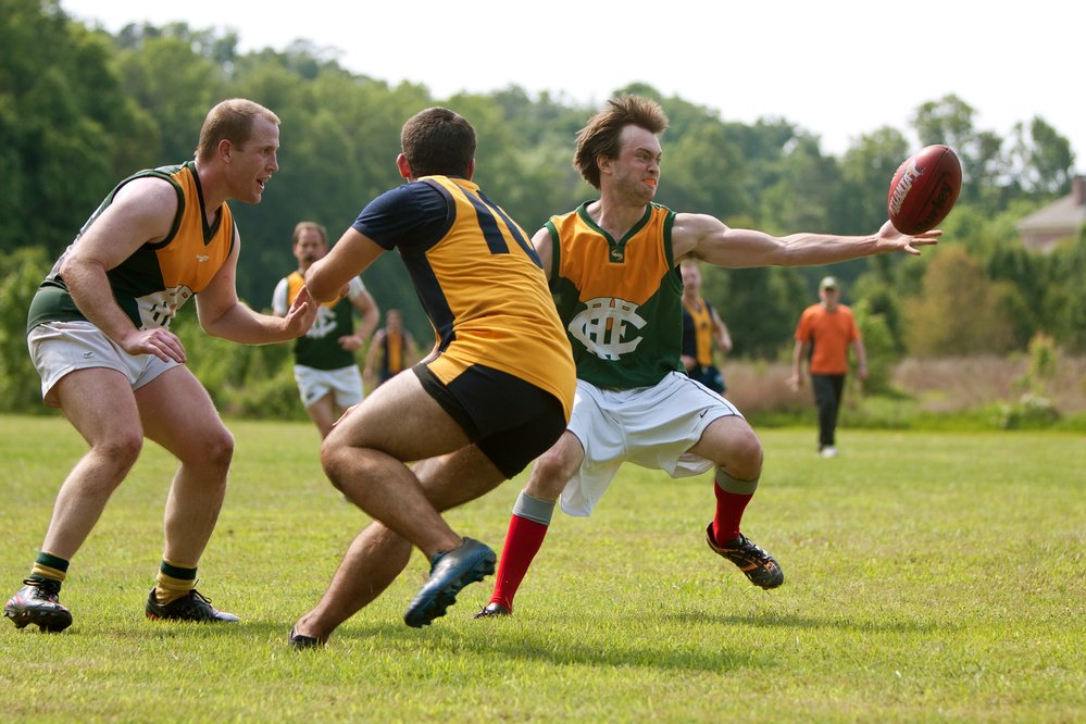 Three amateur Australian Rules players competing for the ball