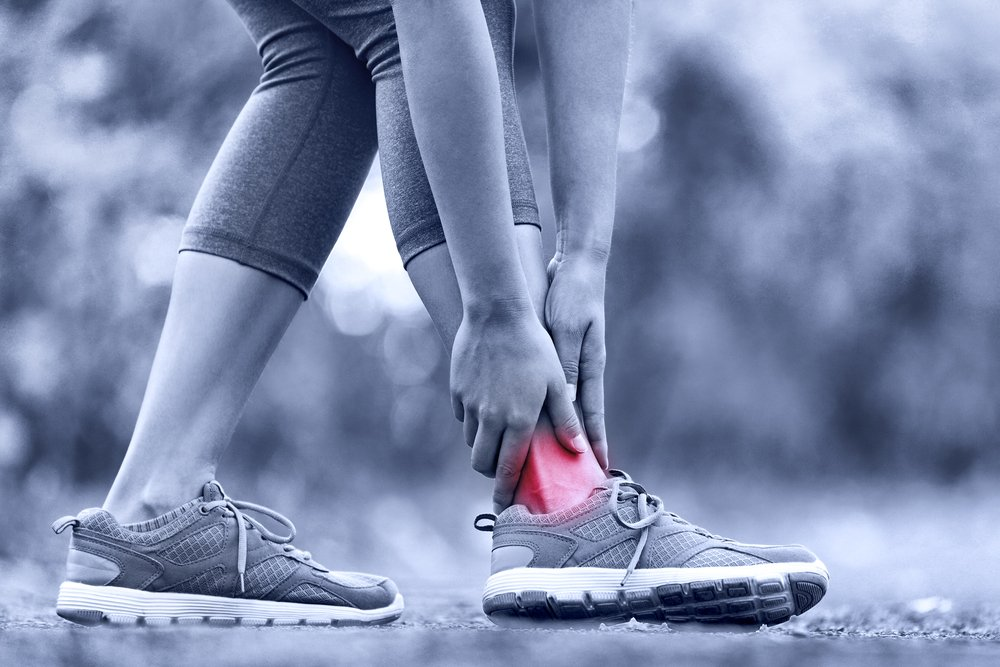 Female runner touching foot in pain due to injured ankle