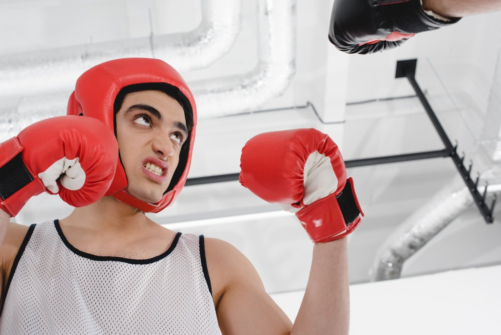 A young male boxer wearing a head protector and boxing gloves, to protect against injury the the right gear