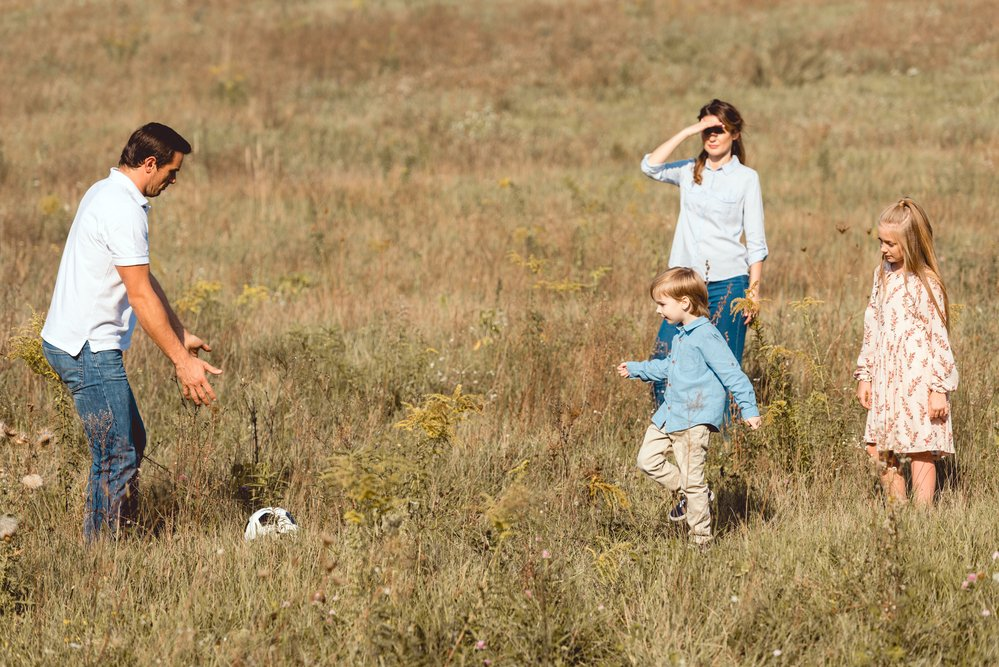 A family playing soccer in a field.The adults helping the kids play safer.
