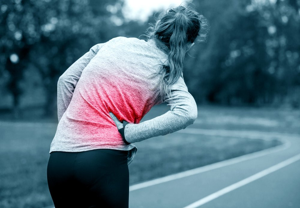 Woman on running track has stitch during workout