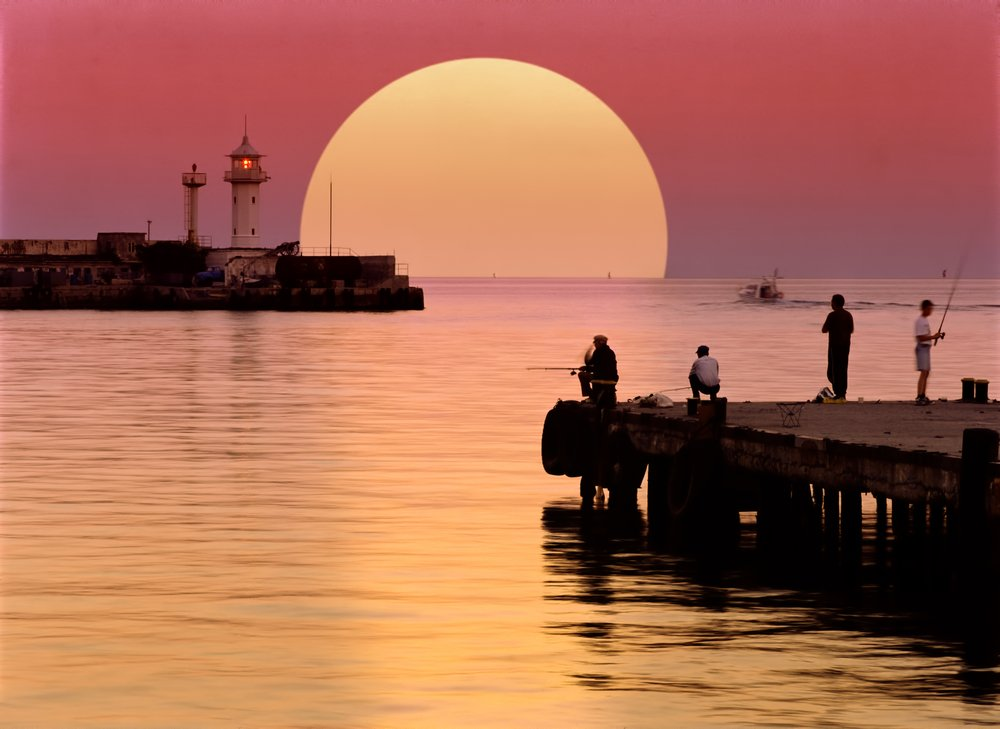 A sunset shot of fishermen fishing on a harbour key and observing fishing safety