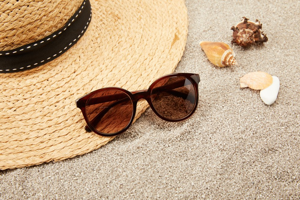 Sunglasses and hat on sand