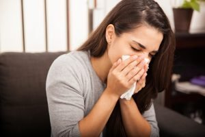 girl with a cold blowing her nose