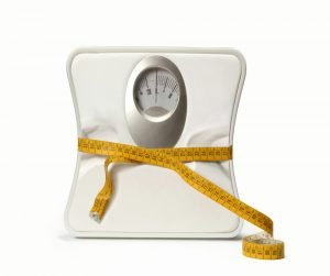 Image of bathroom scale squeezed by tape measure signalling weight loss
