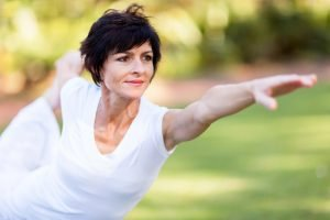 Healthy woman of menopausal age stretching and exercising