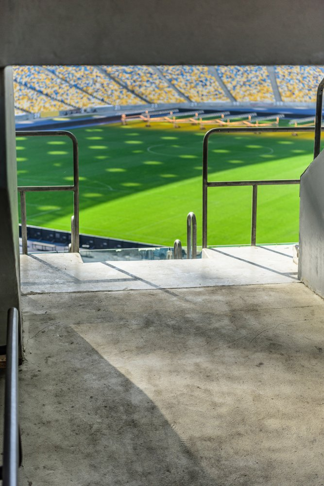 Looking through the entrance of a stadium at a cricket pitch