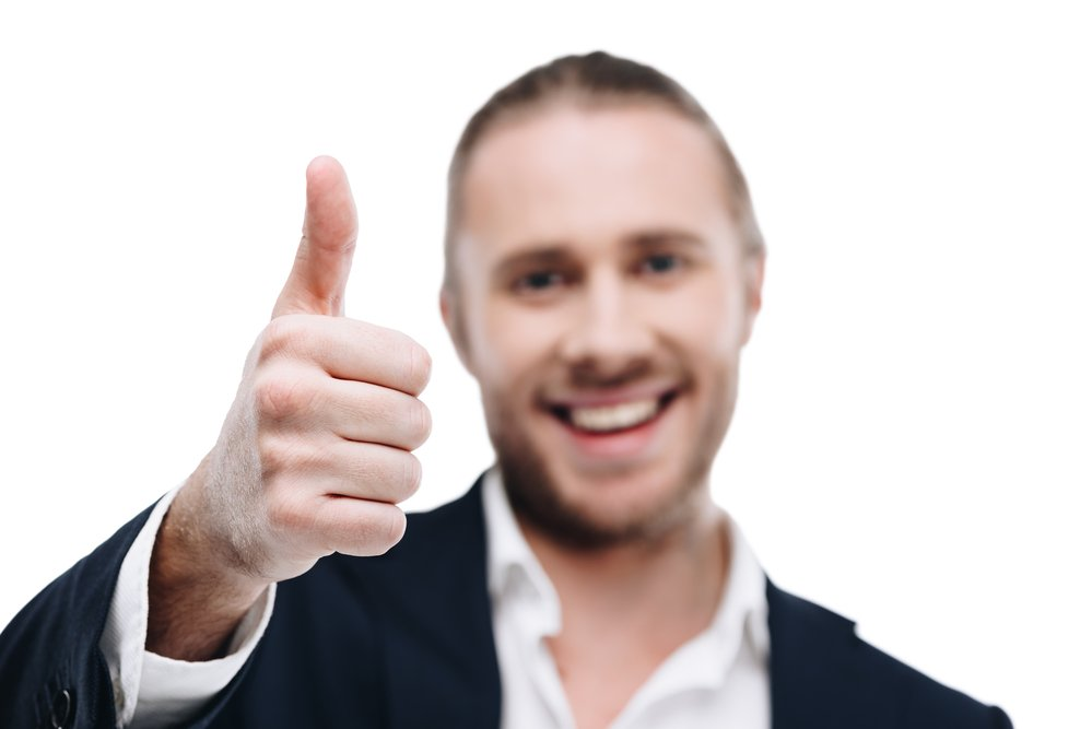 A happy young man with his thumb up, looking positive having taken onboard the advice from our life coach