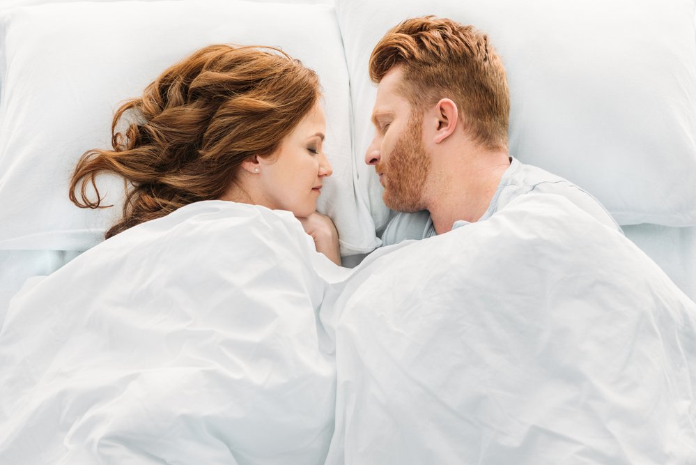 An Atrractive red-headed couple sleeping. Hormones can effect all aspect of your life, including sleep.