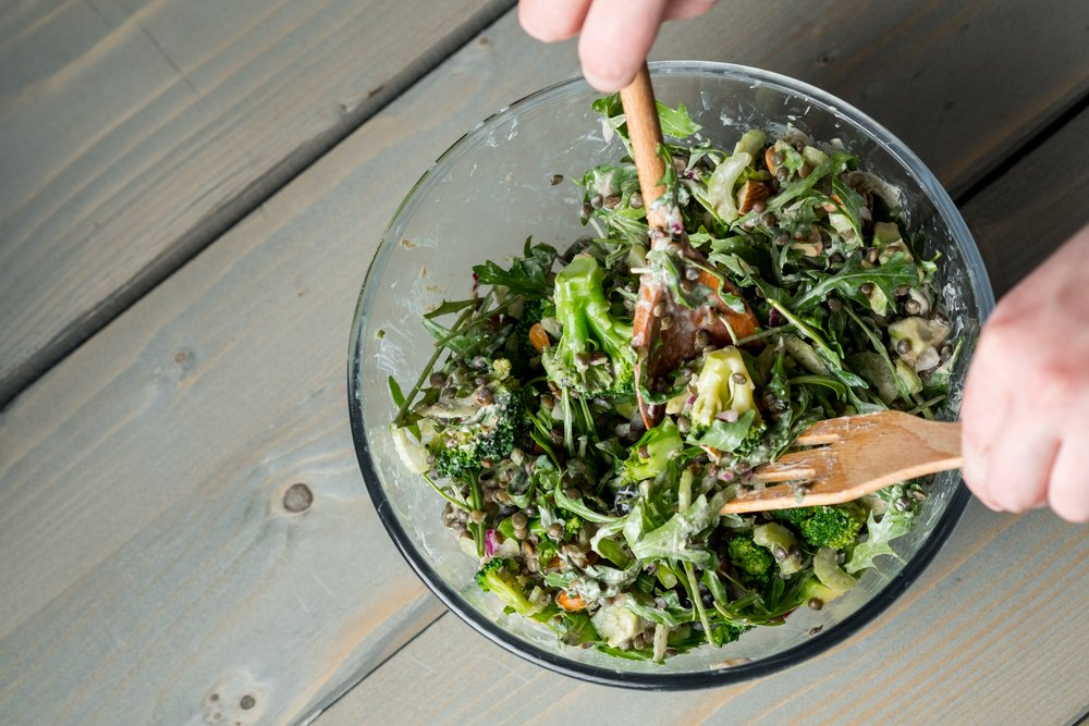 Male hands holding wooden salad tossers, tossing a bowl of leafy greans - perfect for omega-3 fats and to ward off psoriasis