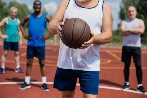 4 older men getting ready to play basketball. the front one holding a basketball