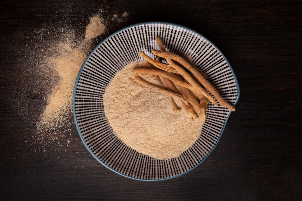 Ashwagandha powder and roots on plate on black background from above. Superfood, adaptogen, nutritional supplement. Used in Ayurveda and Ayurvedic medicine