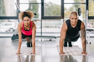 one fit male and one fit female doing planks in a gym