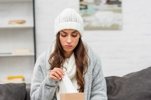 a woman with sinus infections, sitting wrapped up in warm clothes, reaching for a paper tissue.