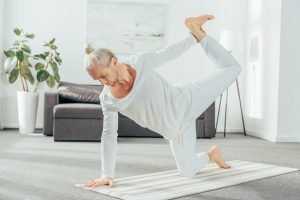 man attempting yoga pose in his living room