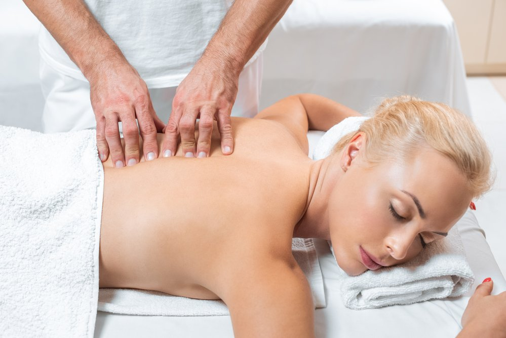 A man practising remedial massage or myotherapy on a woman's back