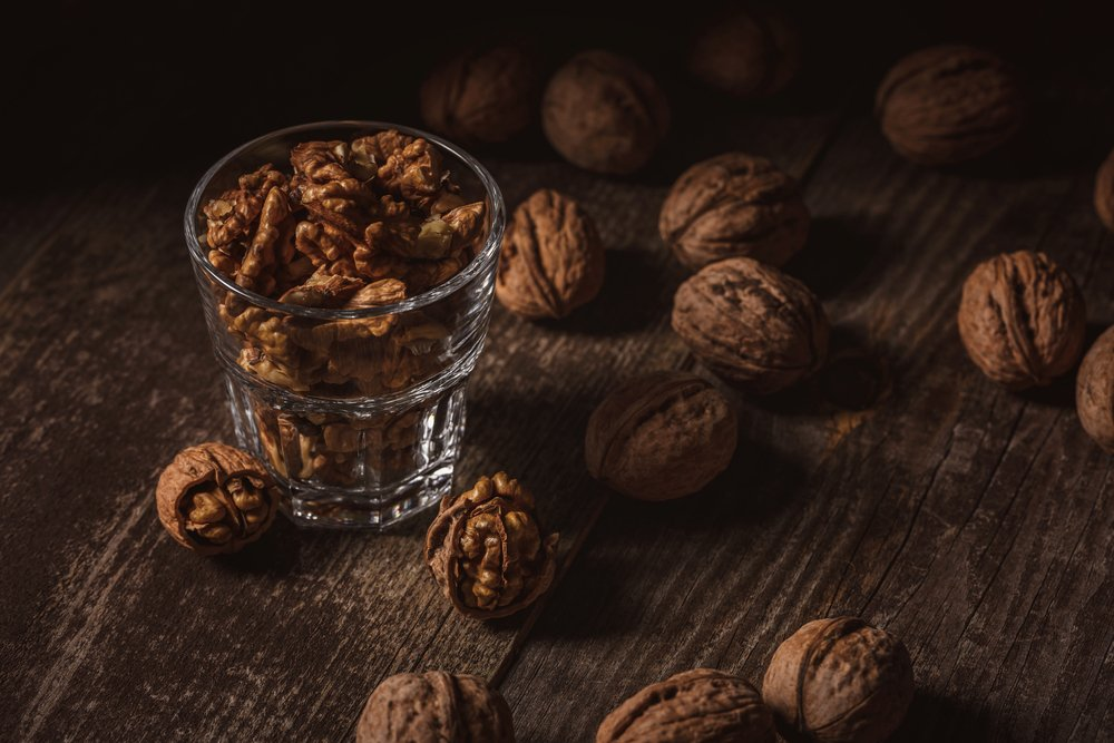 A glass containing omega-3 rich, shelled walnuts, surrounded by unshelled walnuts