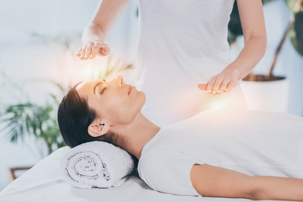 A young woman, lying done and receiving Reiki treatment. If you need more energy, Reiki might help to re-charge you.
