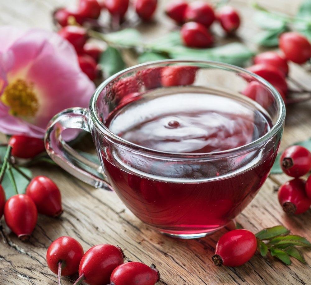 Rosehips and rosehip tea on a wooden table. Examples of nutritional medicine