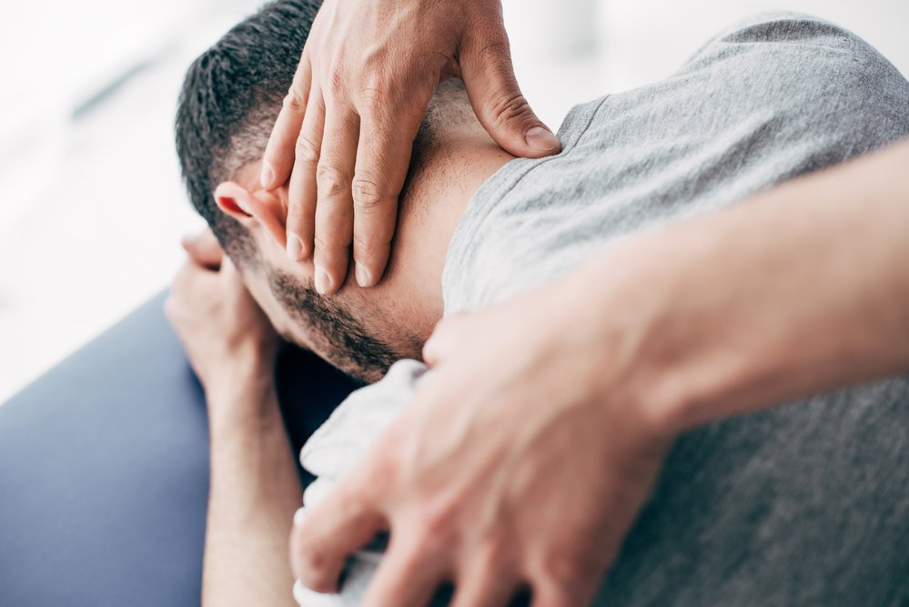 osteopath treating injured man on treatment table