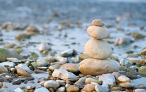 balancing stones on the beach signifying balance in life and health and happiness