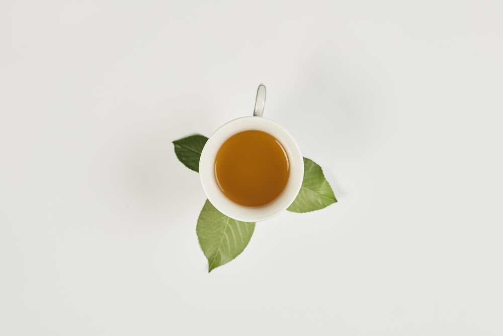 A cup of green tea and tea leaves on a white background. Great for natural health.