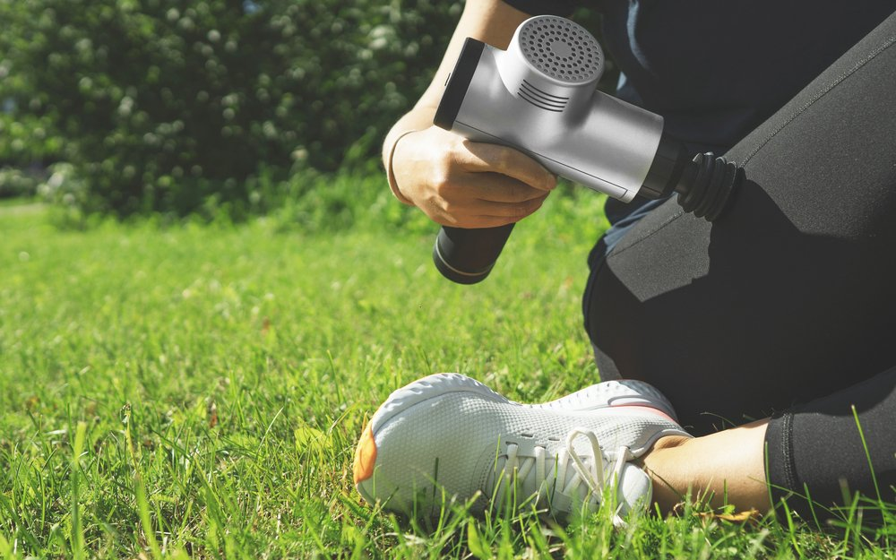 Woman using massage gun on her leg outside in the park