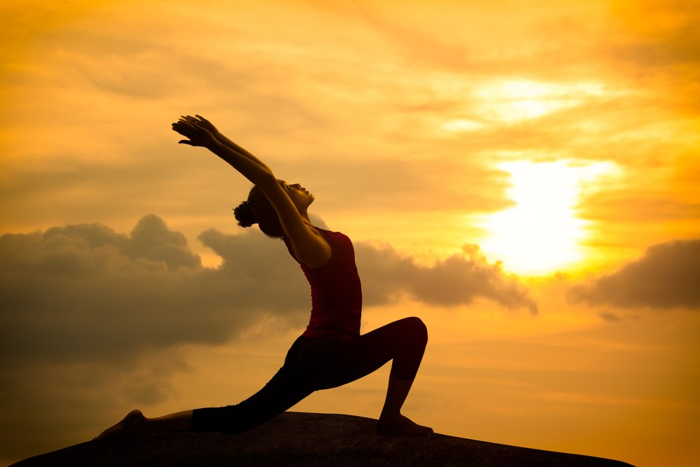 Young woman practicing yoga warrior pose at sunset