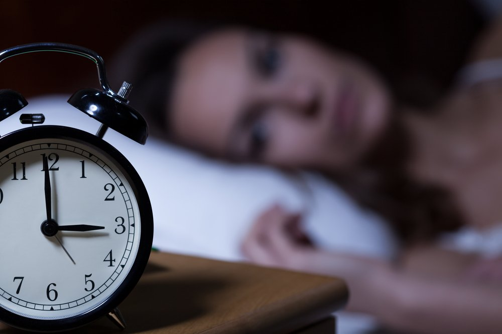 woman unable to sleep anxiously looking at alarm clock