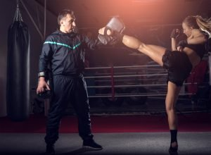 A young woman practising a kickboxing kick with a older male trainer.