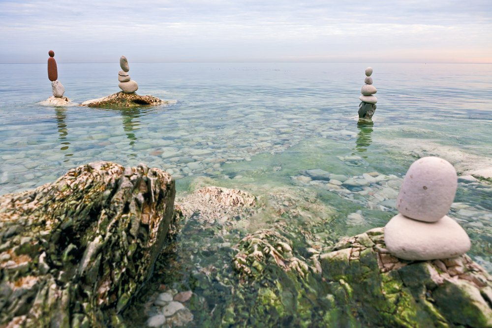 Dealing with stress through mindfulness and meditation.Zen balanced stones on the sea