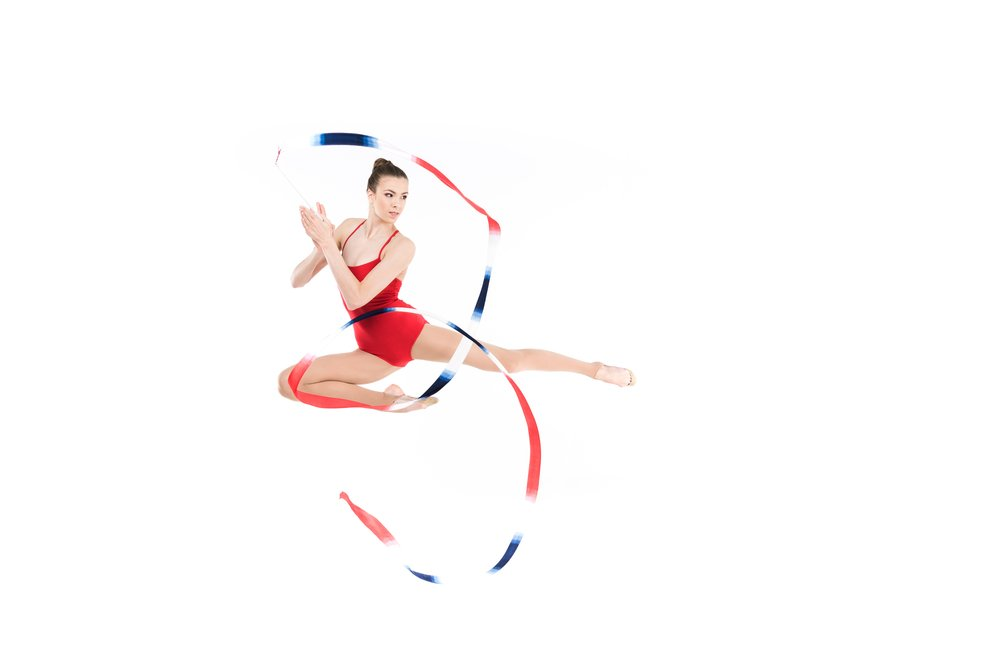 A young woman in a red leotard, performing gymnastics and jumping with a ribbon
