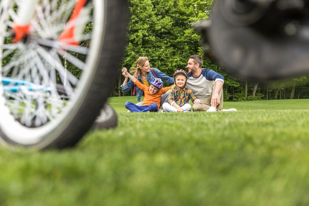 A family taking a rest from a bike ride - perfect for reducing children obesity through safer sport