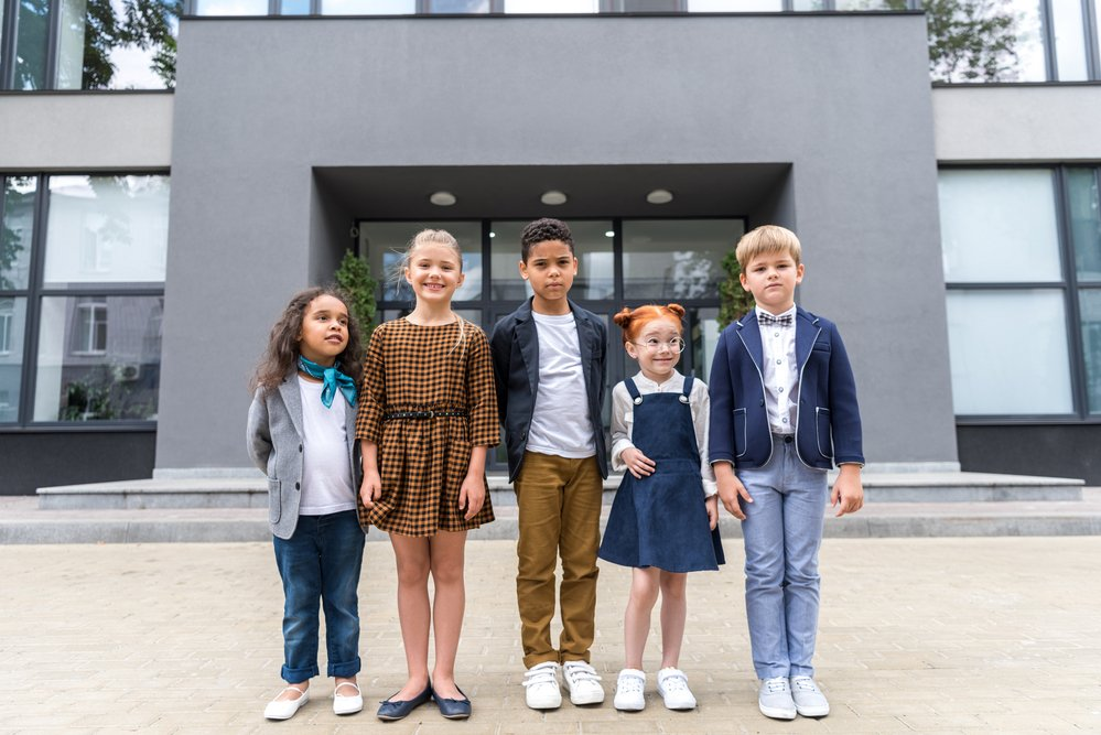 A group of multi-ethnic kids outside a school. Parents can reduce school injuries and keep their children safe.