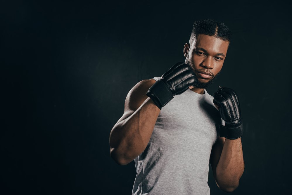 A young man wearing boxing gloves, getting ready to practise his kickboxing