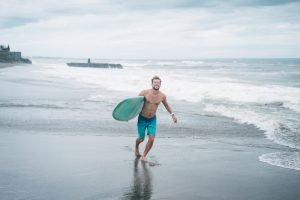 smiling surfer running with surfboard on beach in Bali, Indonesia. He is setting goals for the 'new' him.