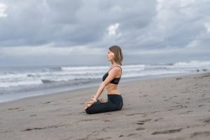 A woman practising mindfulness and dealing with stress through yoga on a beach