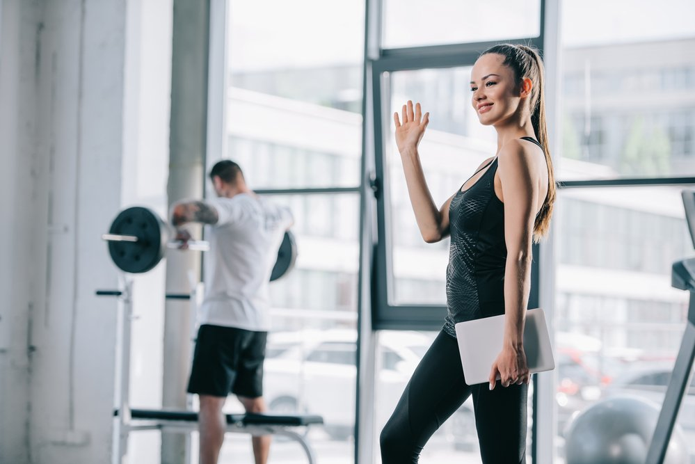 A young female personal trainer. Group exercise or a personal trainer is about preference.