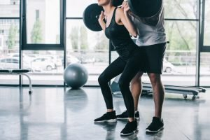 A woman working out with the help of a personal trainer.