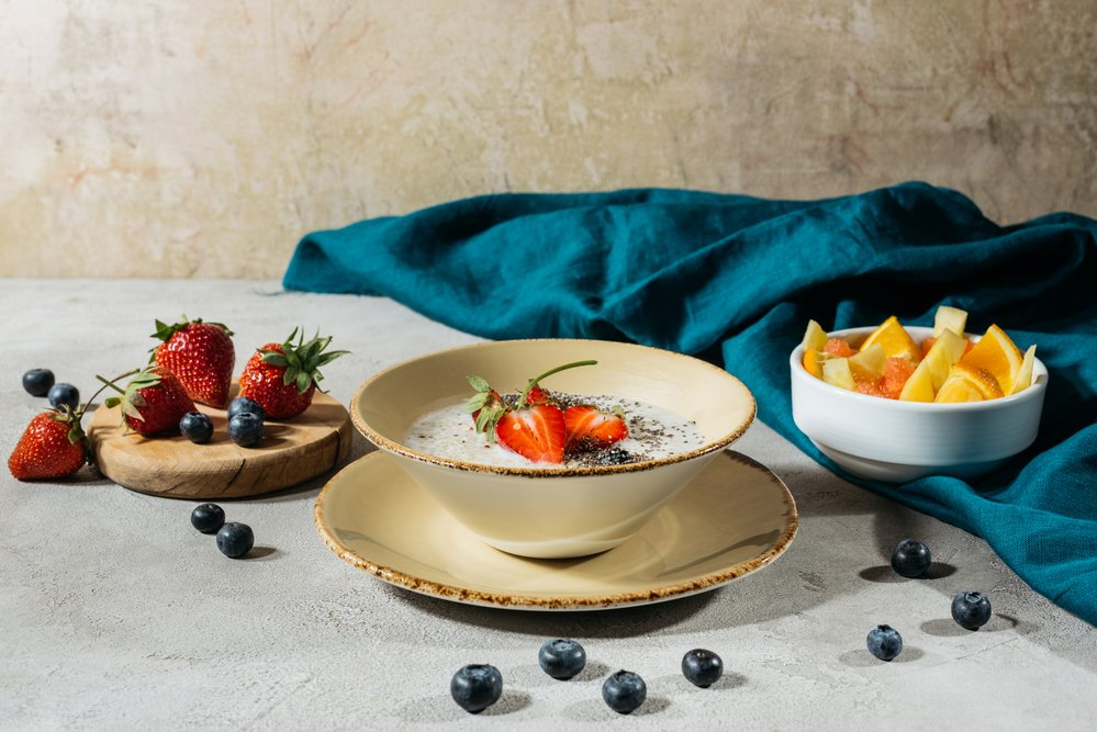 A bowl of healthy breakfast - chia pudding with fresh strawberries and blueberries - perfect for setting you up for the day and to help you in losing fat